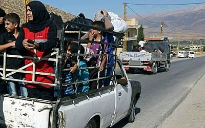 Lebanese citizens in the back of a pickup truck flee Arsal, a predominantly Sunni Muslim town near the Syrian border in eastern Lebanon, Monday, Aug. 4, 2014 (photo credit: AP/Bilal Hussein)