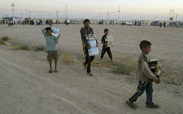 Displaced Iraqis from the Yazidi community carry humanitarian aid at the camp of Bajid Kandala at Feeshkhabour town near the Syria-Iraq border, in Iraq, Saturday, August 9, 2014. (AP/Khalid Mohammed)