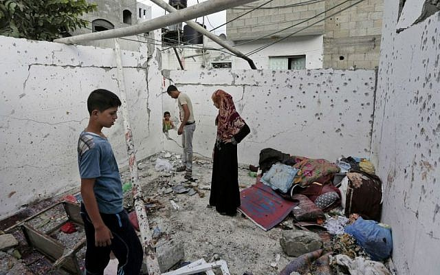 File: Palestinians inspect the damage to a house in the Jebaliya refugee camp that was hit by an Israeli strike in the northern Gaza Strip, Sunday, Aug. 3, 2014.  (photo credit: AP/Lefteris Pitarakis)