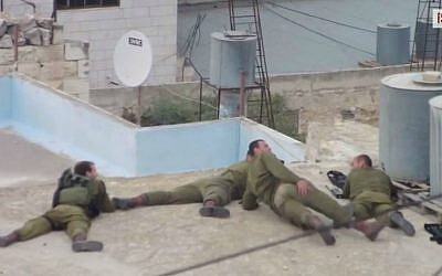 IDF soldiers apparently mocking a Palestinian who has just been shot in the leg. (screen capture: YouTube/  ISM Palestine)