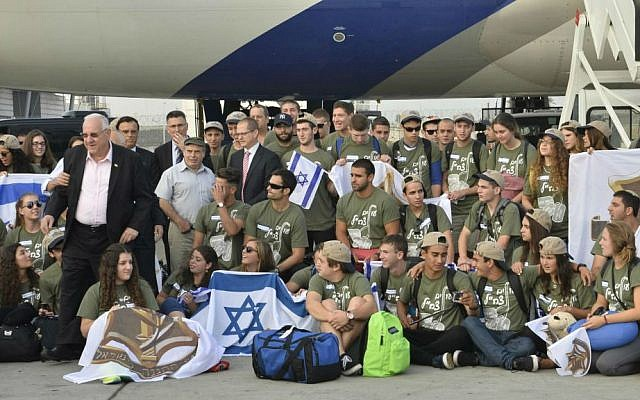 President Reuven Rivlin (L) with some of the more than 100 men and women who immigrated to Israel to join the IDF, Ben Gurion airport, August 12, 2014. (photo credit: Nefesh B'Nefesh)