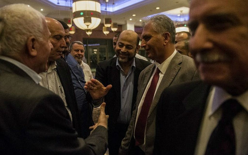 Hamas deputy leader Moussa Abu Marzouk (center) shakes hands with the head of the Palestinian delegation Azzam al-Ahmad (left) upon their arrival at a Cairo hotel after a meeting with senior Egyptian intelligence officials, August 11, 2014. (photo credit: AFP/Khaled Desouki)