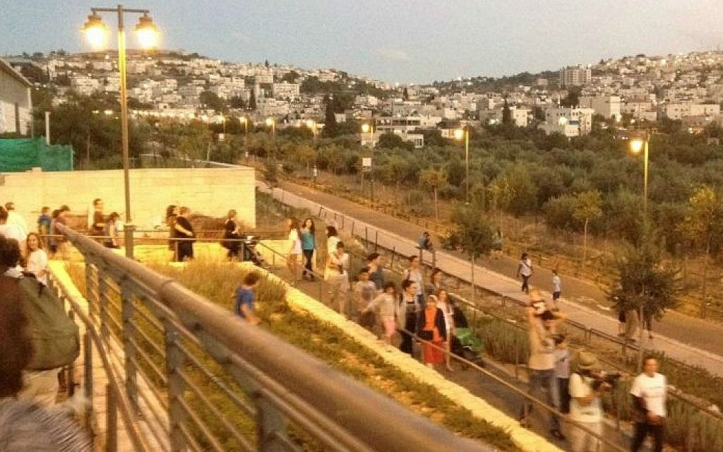 Gathering with members of the larger Hand in Hand community at Jerusalem's Train Track Park for a coexistence walk (photo credit: Jessica Steinberg/Times of Israel)