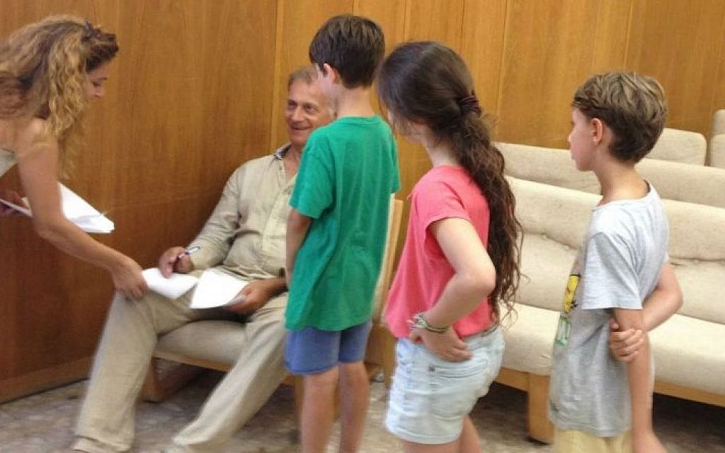 Fans line up for autographs from Matti Caspi, the iconic musician and singer who showed up at Kibbutz Be'eri for an impromptu concert, Thursday, July 31, 2014. (photo credit: Jessica Steinberg/Times of Israel)
