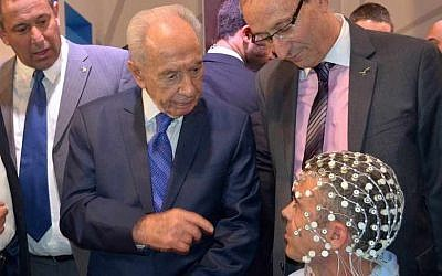 Former president Shimon Peres checks out ElMindA's technology at the 2013 Presidential Conference in Jerusalem. (photo credit: Courtesy ElMindA)