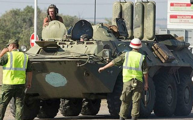 Military road police direct one of several military vehicles of Russian peacekeeping forces to turn to customs control zone about 28 kilometers from Ukrainian border, Rostov-on-Don region, Russia, Friday, Aug. 15, 2014 (photo credit: AP/Pavel Golovkin)