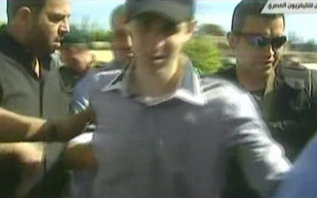 Hamas's Raed Al-Attar (center, partially obscured) with IDF soldier Gilad Shalit (photo credit: Youtube screenshot)