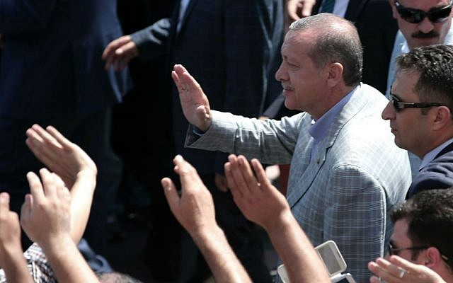 Then-Turkish Prime Minister Recep Tayyip Erdogan salutes cheering supporters at a polling station during the presidential elections in Istanbul, Turkey, Sunday, Aug. 10, 2014. (photo credit: AP/Emrah Gurel)