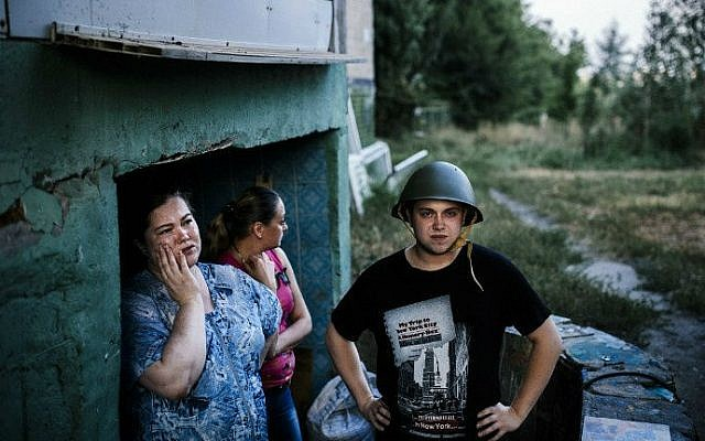 People stand at the entrance of a makeshift bomb shelter in Donetsk, on August 10, 2014 (photo credit: AFP/ Dimitar Dilkoff)