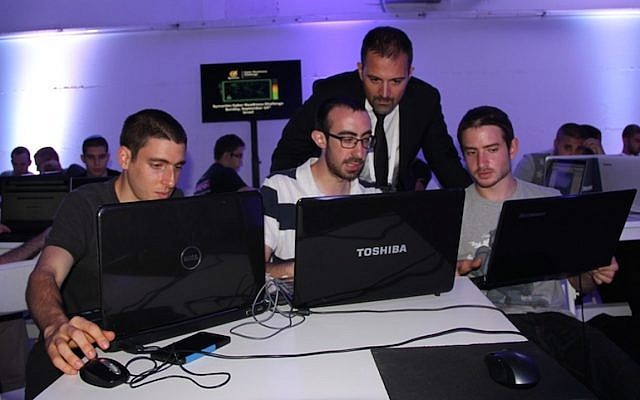 Antonio Forzieri (standing) checks out the work of one of the Israeli teams in the Cyber Challenge contest (Photo credit: Courtesy)