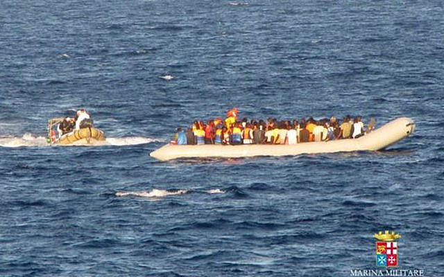 In this handout picture released by the Italian Navy on September 14, 2014 migrants sit in a boat during a rescue operation off the coast of Sicily. More than 2.000 migrants were rescued by Navy ships and patrol boats the last three days as part of the operation called Mare Nostrum. (photo credit: AFP/MARINA MILITARE)