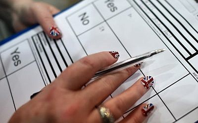 A count observer with Union Jack-painted fingernails looks on as ballot papers are counted in the Aberdeen Exhibition and Conference Centre in Aberdeen, on September 18, 2014, immediately after the polls close in the referendum on Scotland's independence. (photo credit: Ben Stansall/AFP)