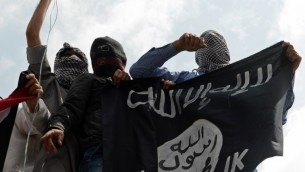 Illustrative photo of men holding up an Islamic State flag on July 18, 2014. (AFP/Tauseef Mustafa)