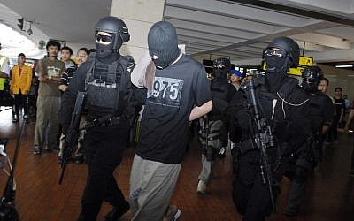 Elite Indonesian anti-terror police from Densus 88 escort four Turks arrested on arrival at Jakarta airport on September 14, 2014. (photo credit: AFP Photo/Bima Sakti)