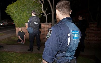 "A handout photo taken and released on September 18, 2014, shows Australian Federal Police officers detaining a suspect in Sydney after Australia's largest ever counter-terrorism raids detained 15 people and disrupted plans to ""commit violent acts"", including against random members of the public that reportedly involved a beheading on camera. photo credit: AFP/AUSTRALIAN FEDERAL POLICE)"