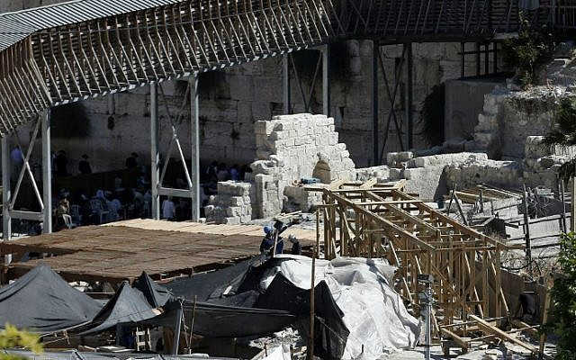 Workers dismantle a wooden ramp (foreground) that was intended to connect to the al-Aqsa mosque complex in Jerusalem on September 10, 2014.  (photo credit: Thomas Coex/AFP)