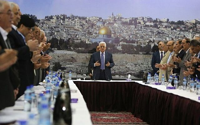 Palestinian Authority President Mahmoud Abbas and his government recite a prayer during a meeting in Ramallah on September 11, 2014. (Photo credit: AFP/ ABBAS MOMANI)