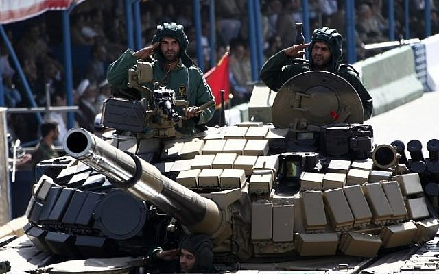 Iranian soldiers salute from a tank during the annual military parade marking the anniversary of Iran's war with Iraq (1980-88) in Tehran, on September 22, 2014 (Behrouz Mehri/AFP)