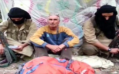 An image grab taken from a video released by Jund al-Khilafah via YouTube on September 22, 2014, allegedly shows French tourist, Herve Gourdel (center), sitting between two armed jihadists at an undisclosed location. (photo credit: AFP/HO/Jund al-Khilafah via YouTube)