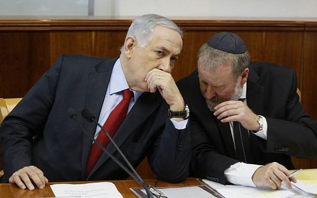 Prime Minister Benjamin Netanyahu, left, listens to cabinet secretary Avichai Mendelblit during a special cabinet meeting in Jerusalem on September 23, 2014. (photo credit: AFP PHOTO/POOL/GALI TIBBON)