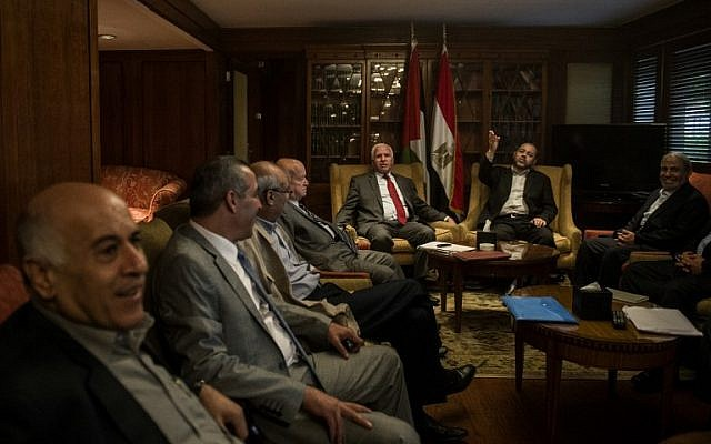 Chief Palestinian negotiator Azzam al-Ahmad (seated C-L) of the mainstream Fatah movement and Hamas's exiled deputy leader Mussa Abu Marzuk (2nd R) are pictured with members of their delegations at a hotel in Cairo following reconciliation talks on September 24, 2014 in the Egyptian capital. (photo credit: AFP/Khaled Desouki)