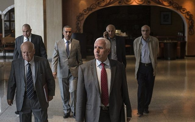 Chief Palestinian negotiator Azzam al-Ahmad (C) of the mainstream Fatah movement walks to a meeting with a Hamas delegation at a hotel in Cairo following reconciliation talks on September 24, 2014 in the Egyptian capital. (photo credit AFP/Khaled Desouki)