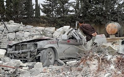 A Syrian man looks at a damaged car under rubble, following a reported US-led coalition airstrike against the headquarters of al-Nusra Front, 20 km west of the northern city of Aleppo on September 25, 2014 (photo credit: AFP/SAMI ALI)