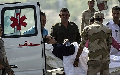 Former Egyptian president Hosni Mubarak is wheeled out of an ambulance outside the Maadi military hospital in Cairo on September 27, 2014, before boarding a helicopter that transported him to court. (photo credit: AFP/Khaled Desouki)