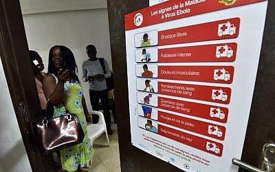 A woman speaks next to an Ebola awareness poster in the Ivorian Popular Front headquarters in Abidjan after they were vandalized on September 1, 2014. (photo credit: AFP/Sia Kambou)