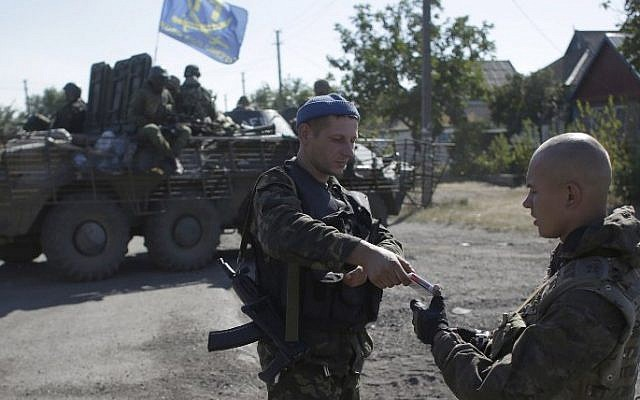 Ukrainian servicemen smoke cigarettes during a pause in a patrol on the border of the Donetsk and Luhansk regions near the town of Debaltseve on September 5, 2014. (Anatoli Stepanov/AFP)