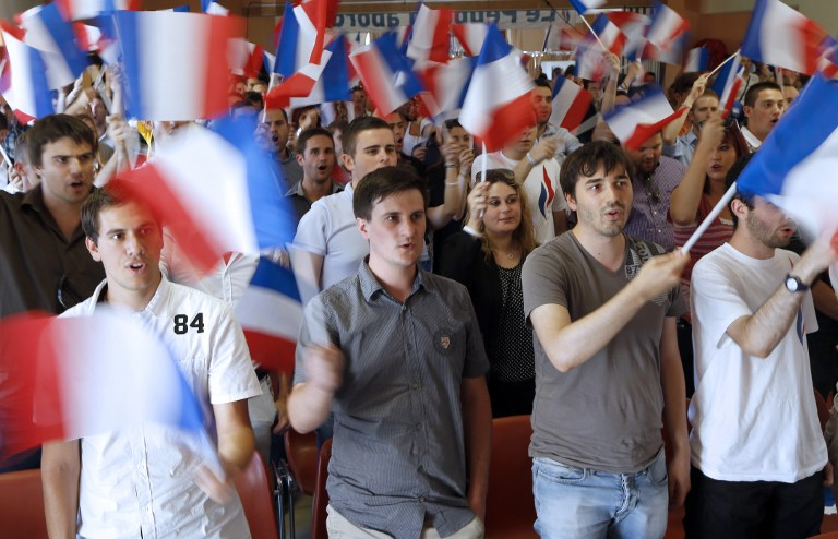 Members of France's far-right National Front wave French flags as they attend the party's summer youth congress in Frejus on September 7, 2014. photo credit: AFP/VALERY HACHE)