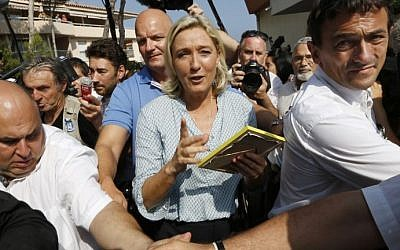 France's far-right National Front leader Marine Le Pen leaves after delivering a speech during the party's summer youth congress in Frejus on September 7, 2014. photo credit: AFP/VALERY HACHE)