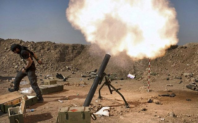 FILE: An Iraqi militia fighter from Shiite cleric Moqtada al-Sadr's Saraya al-Salam (Peace Brigade), fires a mortar during heavy clashes with Islamic State (IS) fighters in Tuz Khurmatu in Salaheddin province about 88 kilometres (55 miles) south of Kirkuk on August 31, 2014.  (photo credit: AFP/ JM Lopez)