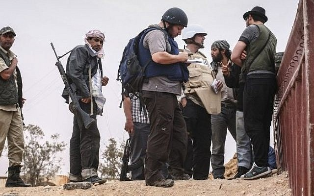 File photo dated June 02, 2011 courtesy Etienne de Malglaive shows American journalist Steven Sotloff (center with dark helmet) talking to Libyan rebels on Al Dafniya front line, 25 km west of Misrata. (Photo credit:AFP PHOTO HANDOUT- © ETIENNE DE MALGLAIVE)
