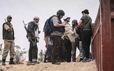 File photo dated June 02, 2011 courtesy Etienne de Malglaive shows American journalist Steven Sotloff (center with dark helmet) talking to Libyan rebels (photo via AFP)