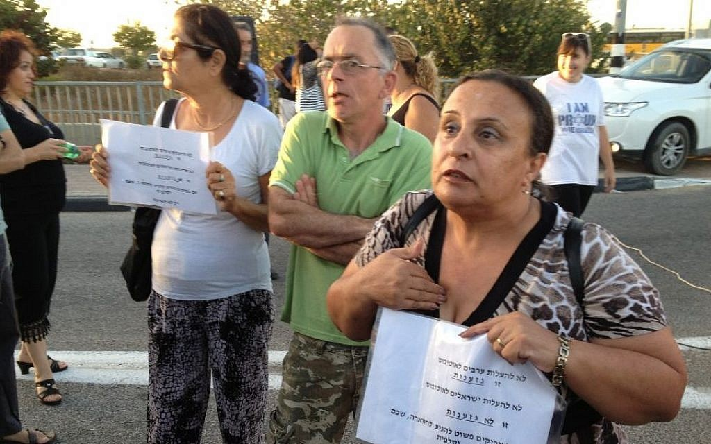 "Ariel resident Ilanit Sheik holds a sign reading ironically ""not letting Arabs on the bus is racism, not letting Israelis on the bus is not racism,"" September 4, 2014 [photo credit: Elhanan Miller/Times of Israel]"