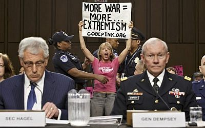 Members of the anti-war activist group CodePink interrupt a Senate Armed Services Committee hearing with Defense Secretary Chuck Hagel, left, and Army Gen. Martin Dempsey, chairman of the Joint Chiefs of Staff, on Capitol Hill in Washington, Tuesday, Sept. 16, 2014. (AP Photo/J. Scott Applewhite)
