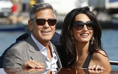 George Clooney, left, and Amal Alamuddin arrive in Venice, Italy, Friday, Sept. 26, 2014, ahead of their wedding. (photo credit: AP Photo/Luca Bruno)