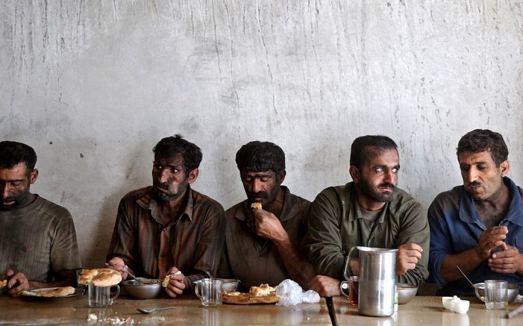 In this Tuesday, Aug. 19, 2014 photo, Iranian coal miners eat lunch at a mine near the city of Zirab 212 kilometers (132 miles) northeast of the capital Tehran, on a mountain in Mazandaran province, Iran. International sanctions linked to the decade-long dispute over Iran's nuclear program have hindered the import of heavy machinery and modern technology in all sectors, and coal mining is no exception. (Photo credit: AP/Ebrahim Noroozi)