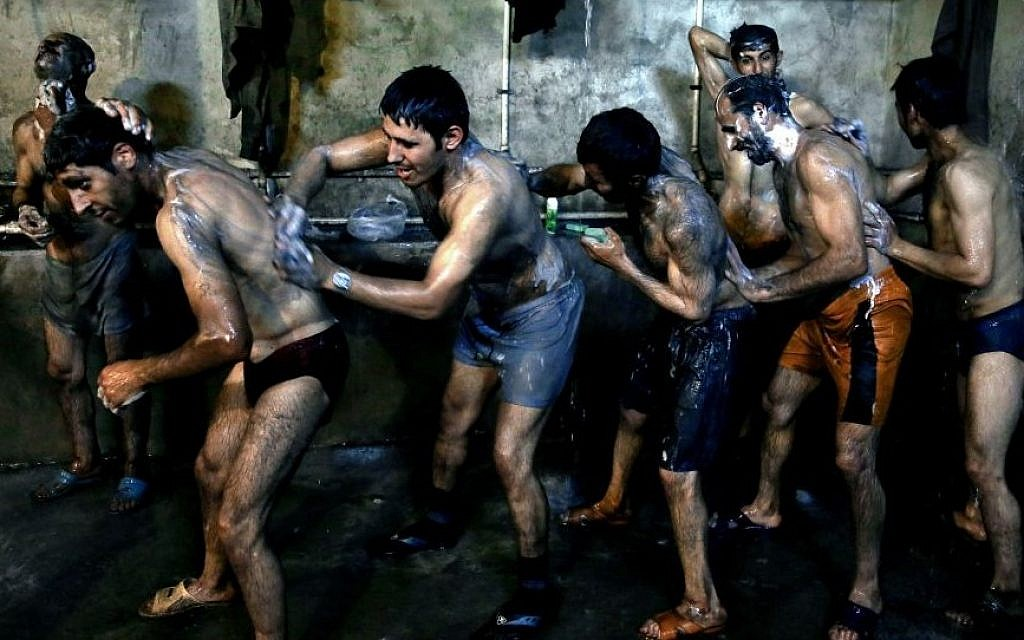 In this Tuesday, May 6, 2014 photo, Iranian coal miners shower after a long day of work at a mine on a mountain in Mazandaran province, near the city of Zirab, 212 kilometers (132 miles) northeast of the capital Tehran, Iran. (Photo credit: AP/Ebrahim Noroozi)