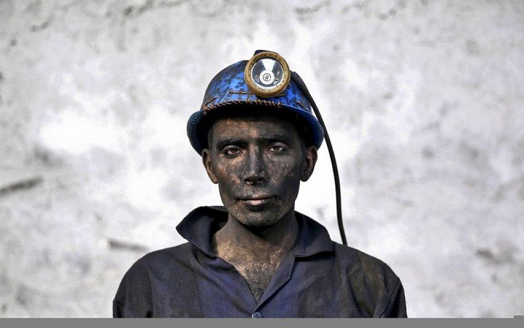 In this Wednesday, May 7, 2014 photo, an Iranian coal miner with his face smeared black from coal poses for a photograph at a mine near the city of Zirab 212 kilometers (132 miles) northeast of the capital Tehran, on a mountain in Mazandaran province, Iran. The workers who put in long hours in often dangerous conditions and make just $300 a month, little more than minimum wage. (Photo credit: AP/Ebrahim Noroozi)