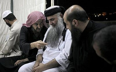 In this Wednesday, Sept. 24, 2014 photo, radical al-Qaida-linked preacher Abu Qatada, center, listens to the renowned jihadi ideologue, Abu Mohammed al-Maqdisi, second left, on the day Abu Qatada was released from Jordanian prison after an acquittal on security charges, in Amman, Jordan. (photo credit: AP photo/Mohammad Hannon)