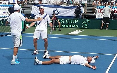 Israel's Andy Ram sprawled on the court following his five-set doubles victory with partner Yoni Erlich, holding racket, against Argentina in a Davis Cup match in Sunrise, Fla., Sept. 13, 2014 (photo credit: Andrea Eidman/JTA)