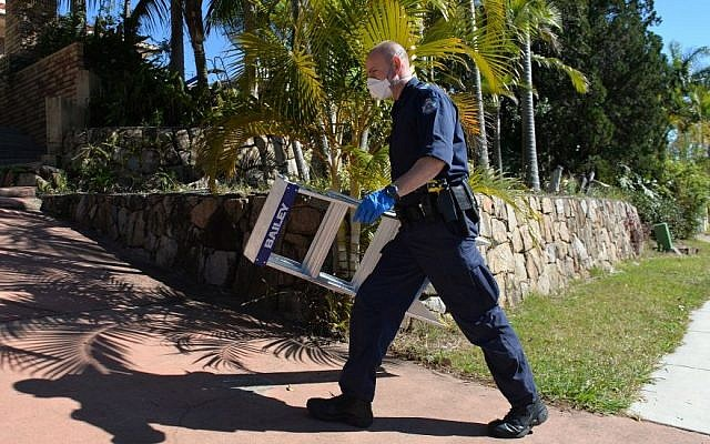 A police officer searches a house in Mount Gravatt, Brisbane, Australia, Thursday, Sept. 18, 2014. (Photo credit: AP/AAP Image, Dave Hunt)