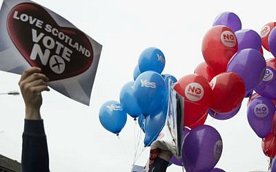 Balloons held by Yes supporters float next to balloons and posters held by No supporters ahead of a vote on Scottish independence, Glasgow, Scotland, Wednesday, Sept. 17, 2014. (photo credit: AP/Matt Dunham)