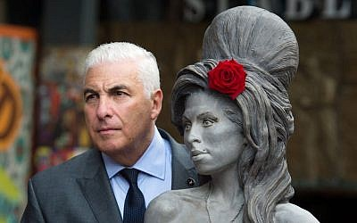 Mitch Winehouse poses for a photo with a statue of his late daughter, Amy Winehouse after it was unveiled in Camden's Stables Market, in London, England, Sunday, on September 14, 2014. (photo credit: AP/Tim Ireland)