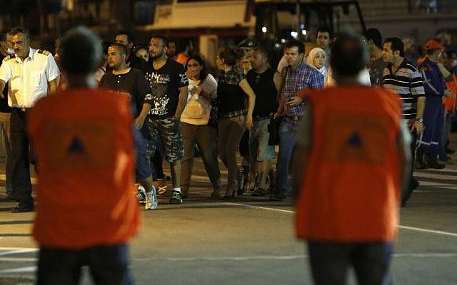A group of migrants disembark from a cruise ship that rescued them from a stranded, smaller boat off the southwestern coast of the east Mediterranean island on Thursday, September 25, 2014. (AP Photo/Petros Karadjias)
