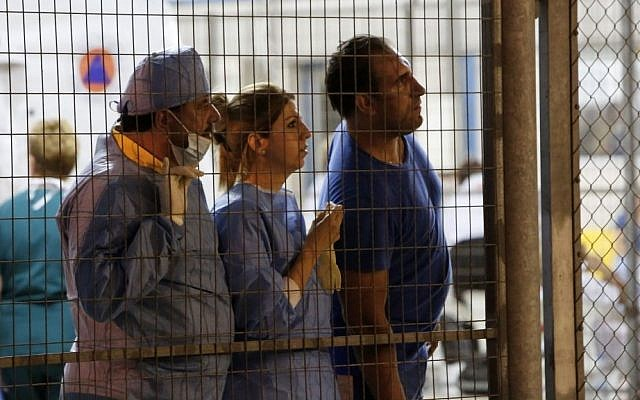 Medical staff wait at Cyprus' main port of Limassol for 345 people to disembark from a cruise ship that rescued them from a stranded, smaller boat off the southwestern coast of the east Mediterranean island on Thursday, Sept. 25, 2014. (AP Photo/Petros Karadjias)