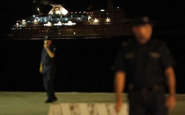 Policemen stand guard as a ship, that picked up some 345 migrants from a small boat stranded off the southwestern coast of Cyprus, arrives at the Mediterranean island's port of Limassol on Thursday, Sept. 25, 2014. (AP Photo/Petros Karadjias)