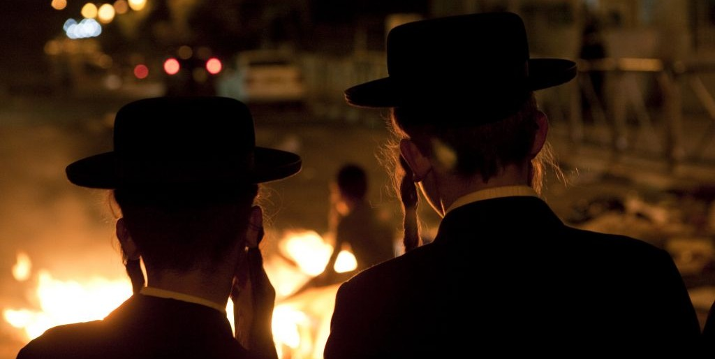 Ultra-Orthodox men watch a fire set during a protest in Mea Shearim. The protest was over the arrest of young ultra-Orthodox men, taken into custody during a demonstration against the opening of a parking lot on the sabbath, in July 2009. (Photo credit: Matanya Tausig/Flash90